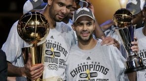 Frenchman Tony Parker (R) of the San Antonio Spurs holds the MVP trophy with teammate Tim Duncan (L) holding the NBA Championship Larry O'Brien trophy after leading the San Antonio Spurs to their fourth NBA title beating the Cleveland Cavaliers 14 June 2007 after Game Four of the NBA Finals at Quicken Loan Arena in Cleveland, Ohio. The Spurs won the game 83-82 to win the best-of-seven game series 4-0.      AFP PHOTO/JEFF HAYNES (Photo credit should read JEFF HAYNES/AFP/Getty Images) ORG XMIT: JTH003